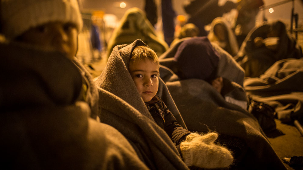 A child waits in line with a group of refugees on the border between Austria and Hungary at Nickesldorf. After crossing on foot from Hungary, the refugees must wait in the cold before buses are available to take them to various camps in Austria