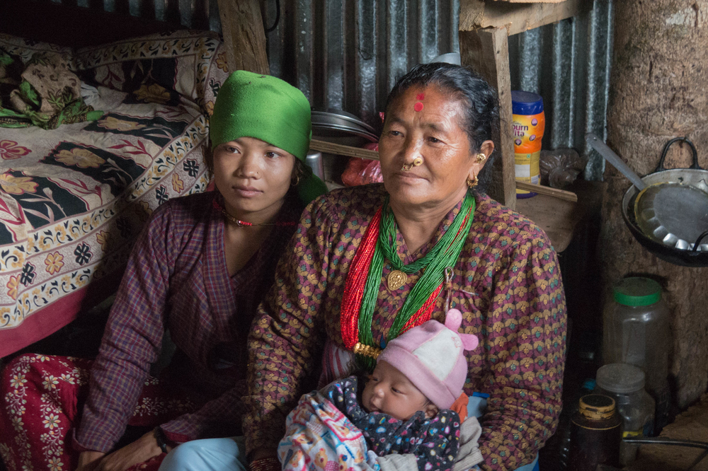 Bimala Thami sits with community health worker  Gauri Thami in October 2015 in the temporary shelter she lives in with her infant in Nepal's Dolakha district after her house was destroyed by a earthquake on 25 April 2015