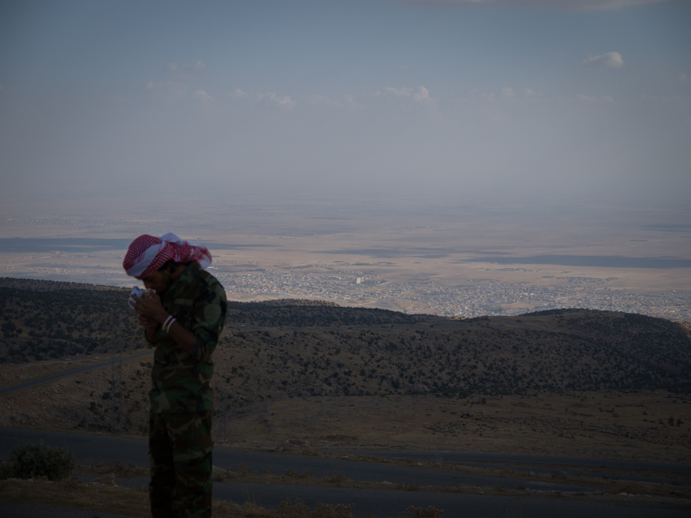 A Kurdish fighter prepares to descend Mount Sinjar to Sinjar City (in the background) where the battle against IS is ongoing.