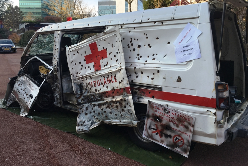 A display outside the 32nd International Conference of the Red Cross and Red Crescent in Geneva shows an ambulance that has been attacked. The states party to the Geneva Convention and national Red Cross and Red Crescent societies adopted a resolution to