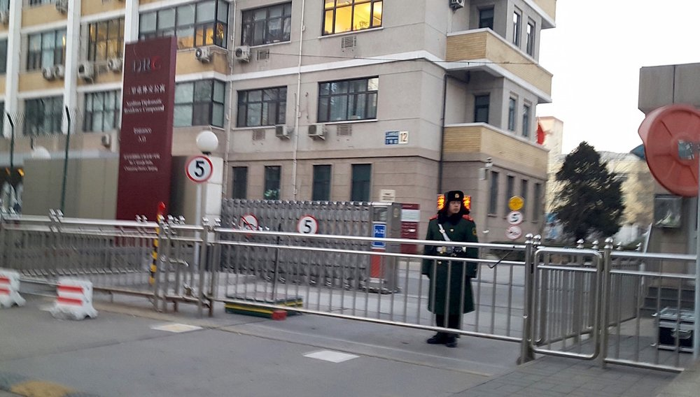 A member of the Chinese People's Armed Police Force stands guard outside the gates of the Sanlitun Diplomatic Residence Compound in Beijing, China, where some foreign NGOs are based