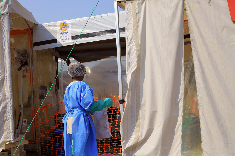 A woman in medical gear outside of a medical tent