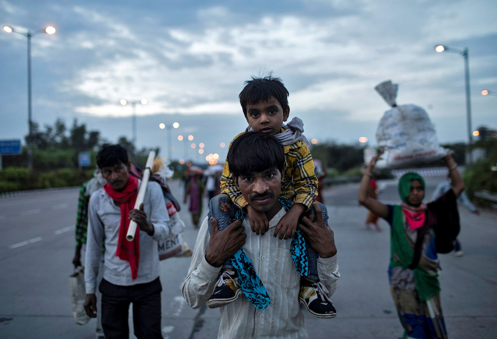 Migrant worker Dayaram Kushwaha carries his five-year-old son as they walk along a road in Delhi during a nationwide lockdown on 26 March. (Danish Siddiqui/REUTERS)
