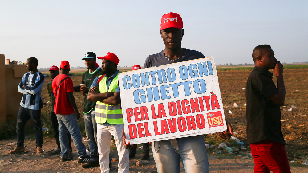 "An African migrant laborer holds a banner reading, ""Against all ghetto, for the dignity of work"""