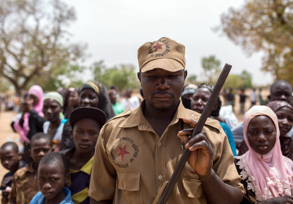 A member of the Koglweogo manages the crowd at a community gathering in the town of Ziniaré