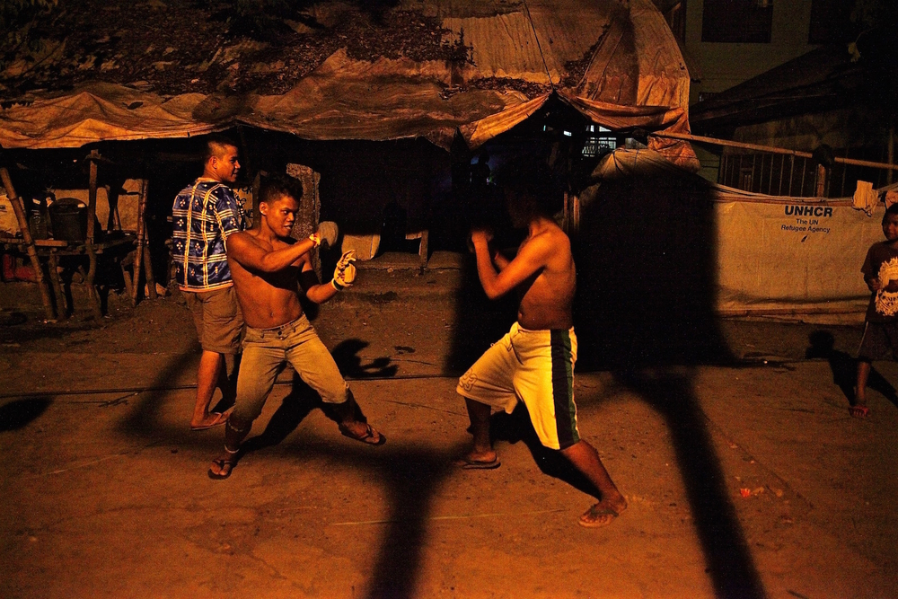 Young Lumad men practise boxing at a displacement camp at a church in Davao City