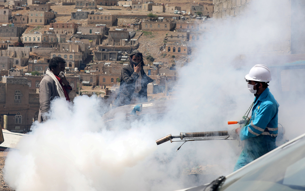 People cover their faces as a health worker fumigates a residential area outside of Sana'a