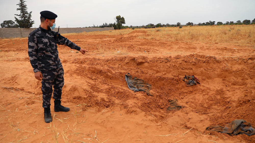 A member of security forces loyal to Libya's Government of National Accord points to a mass grave