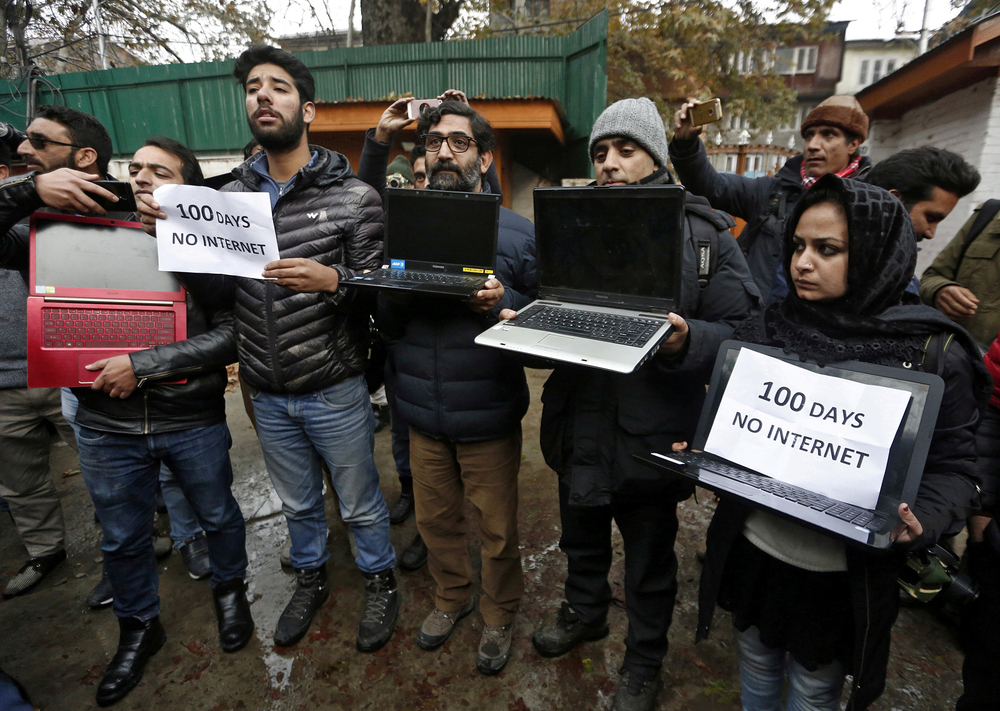 Kashmiri journalists display laptops and placards during a protest