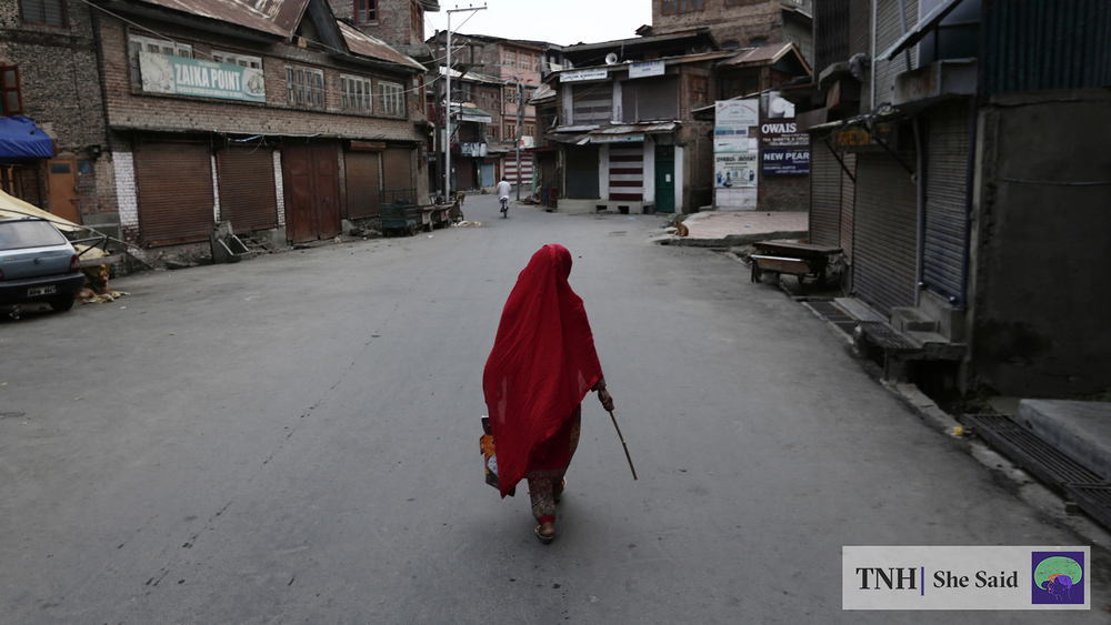 A Kashmiri woman walks through a deserted lane