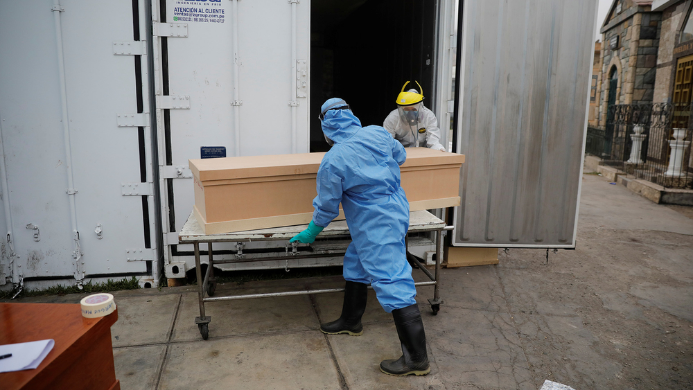 Workers take a coffin to the crematorium at Angel Cemetery in Lima