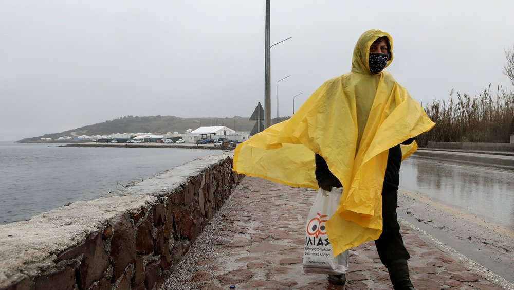 A woman walks along a coastal promenade wearing a yellow rain poncho, and holding a plastic grocery bag. Her face is covered by a mask.