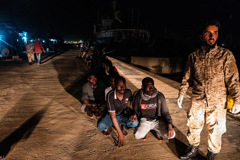 Migrants wait in line at Tripoli's naval base