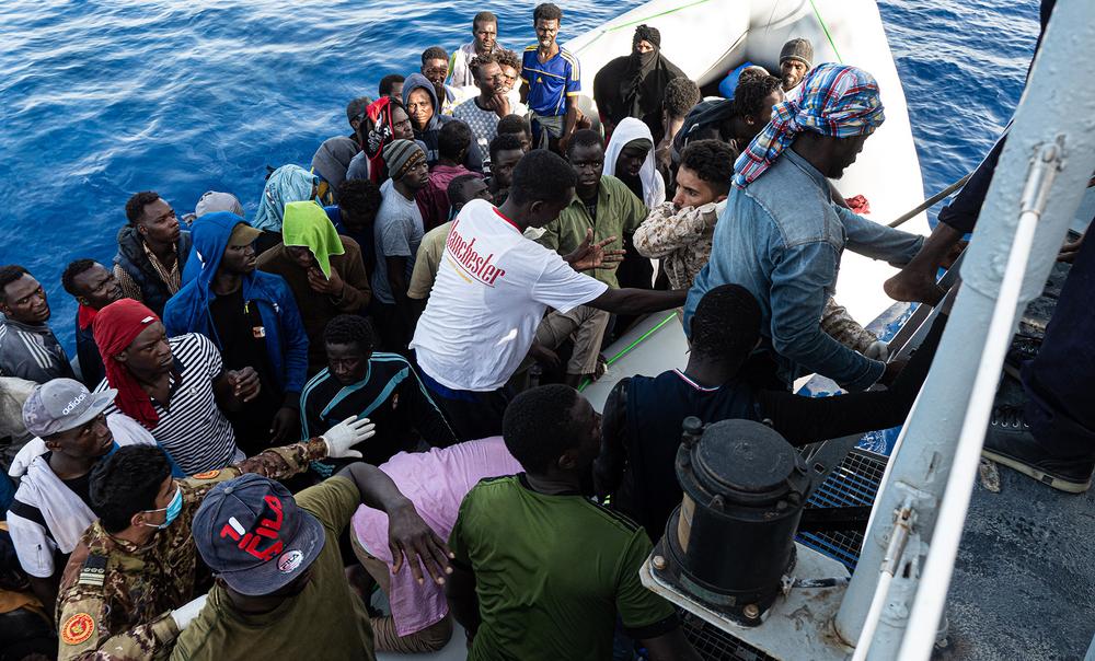 Libya Coast Guard boarding migrants onto a ship