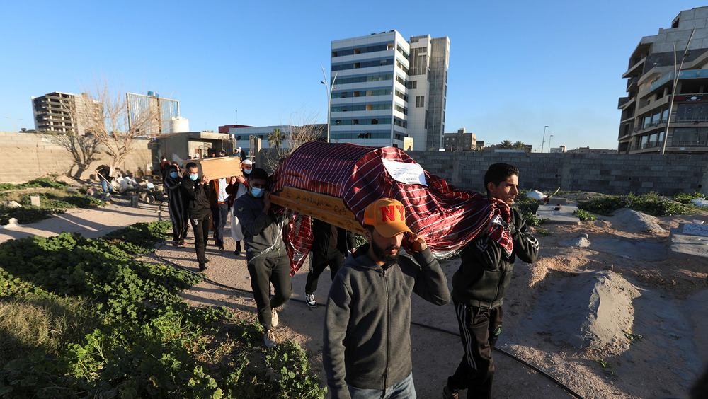 The image shows several men carrying a coffin with the Libya skyline in the background.