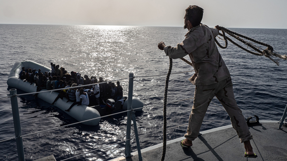 A Libyan Coast Guard sailor throws a rope towards boat carrying migrants