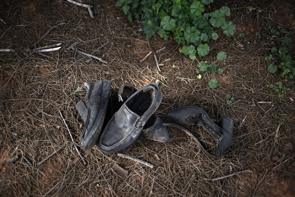 Two pair of muddy shoes – a pair of sneakers and low-heeled pumps – lie on the grass and are pictured from above.