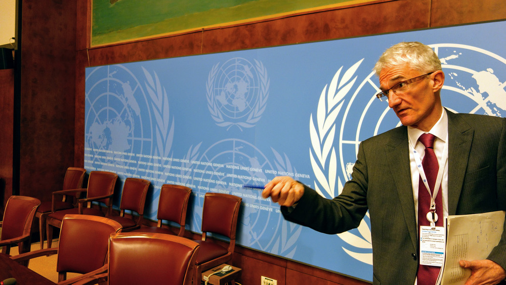 UN humanitarian chief Mark Lowcock stands to the right of the image, looking past the camera and holding out a pen in his hand. Empty seats are pictured in the background, as well as a large poster of the UN's brand.