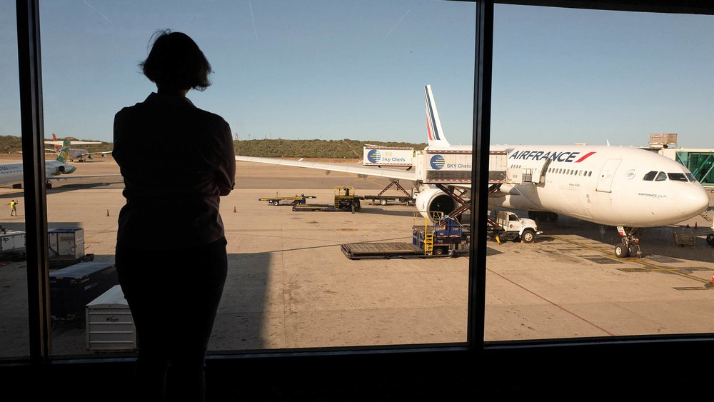 Person stands looking out of an airport window.