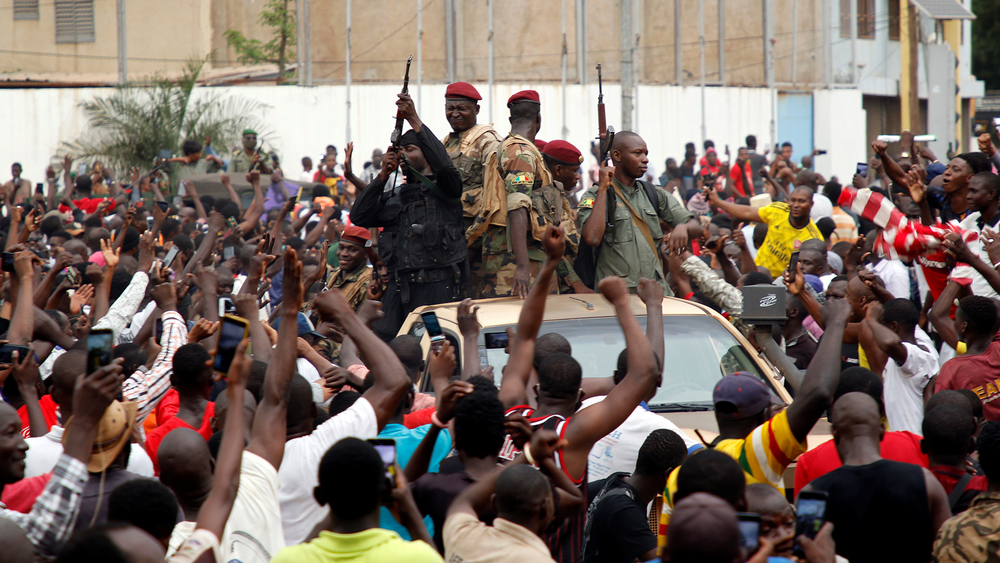 A crowd cheers Malian army soldiers