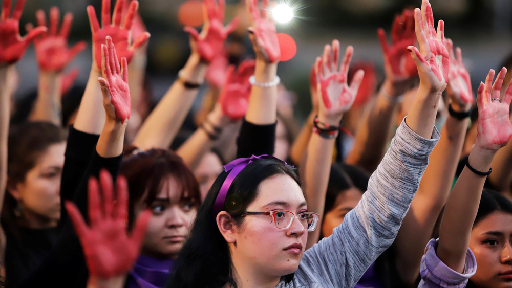 Women raise their hands as they protest against gender violence and femicide in Puebla, Mexico on 22 February 2020.