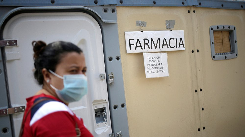 A woman wearing a face mask stands in the forground on the left-hand side of the image, while in the background the is a wall with the sign reading 'farmacia' hanging on it.