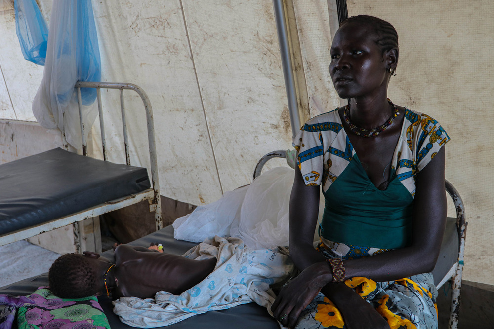 A mother sits with her malnourished child on a bed in Pibor's main health centre.