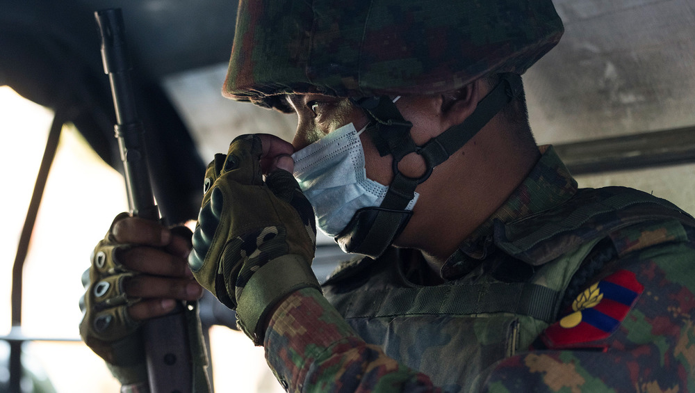 A side profile view of an armed soldier holding a gun, as he adjusts his face mask.