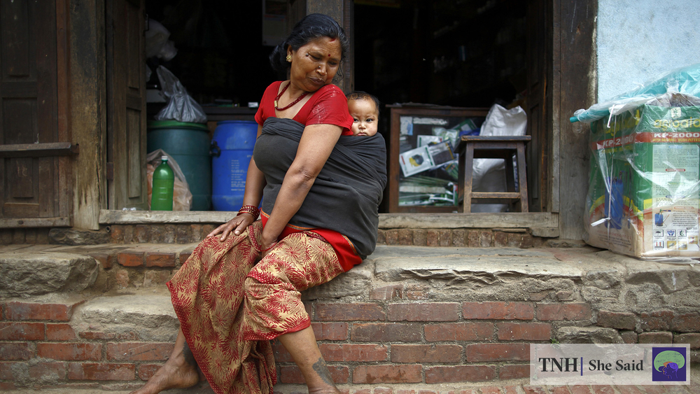 A woman carrying a baby sits outside her shop in the city of Bhaktapur