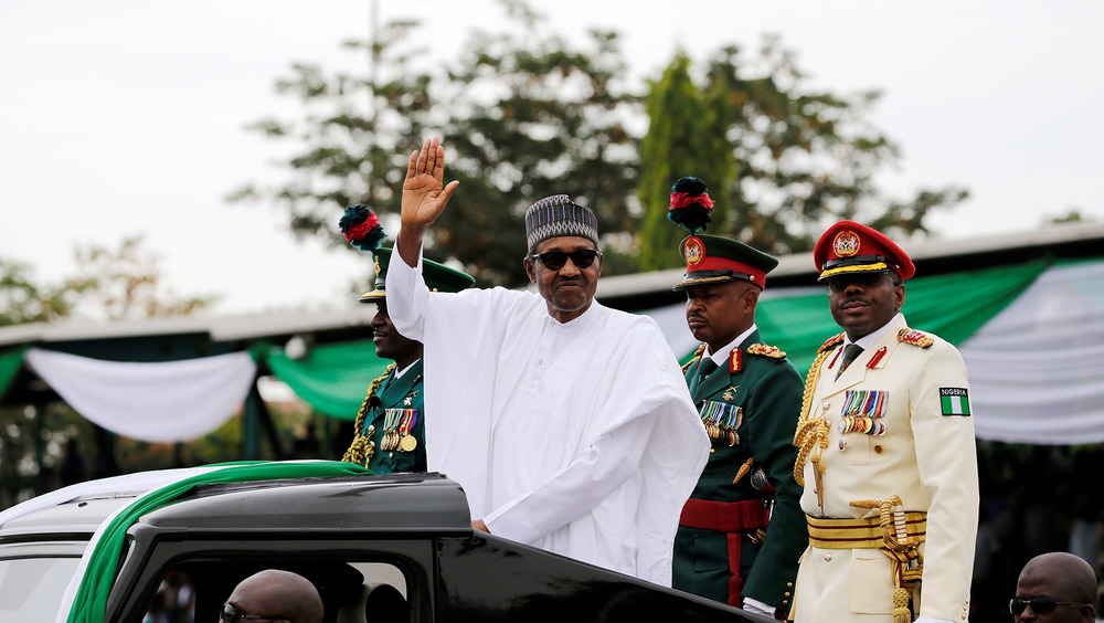 The Nigerian president and several other people wave from the back of a vehicle.