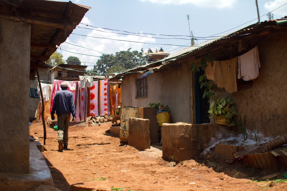 A man walks between homes in Kibera