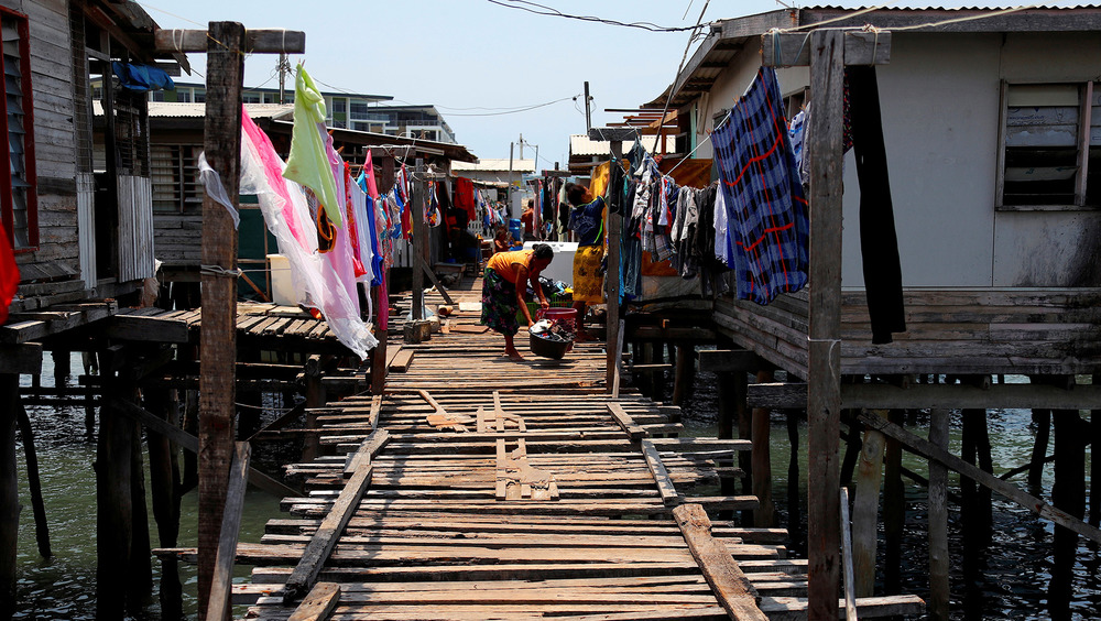 A woman washes clothes on a wooden boardwalk in-between two rows of stilt houses