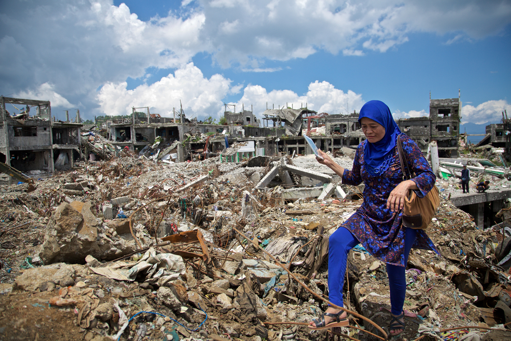 A woman walks through rubble in Marawi in the Philippines