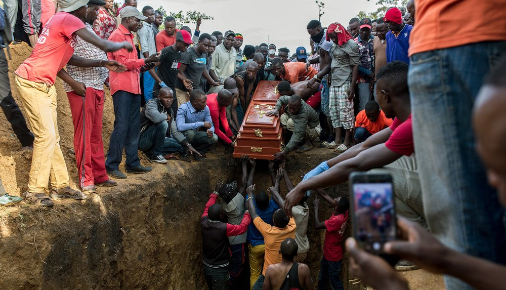 Photo of a coffin being lowered into a mass grave in Ituri province of DRC