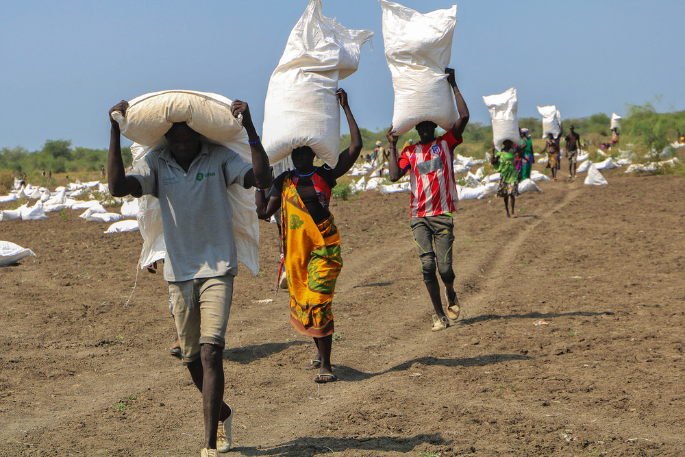 Three residents carry food aid bags on their shoulders as they walk towards the camera