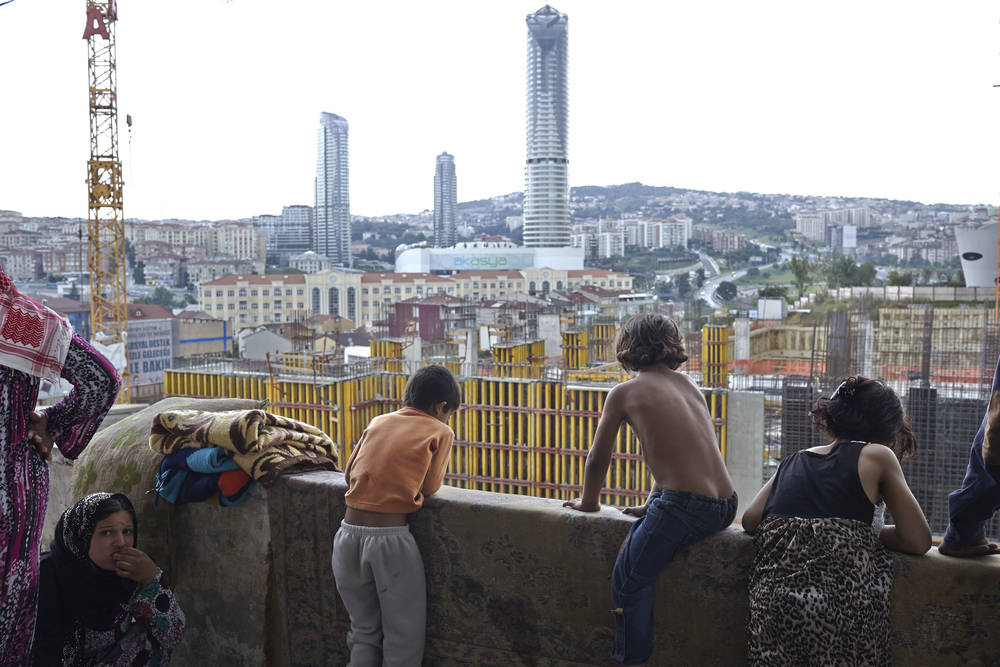 Children look out from the balcony of a tall building onto new construction in Istanbul