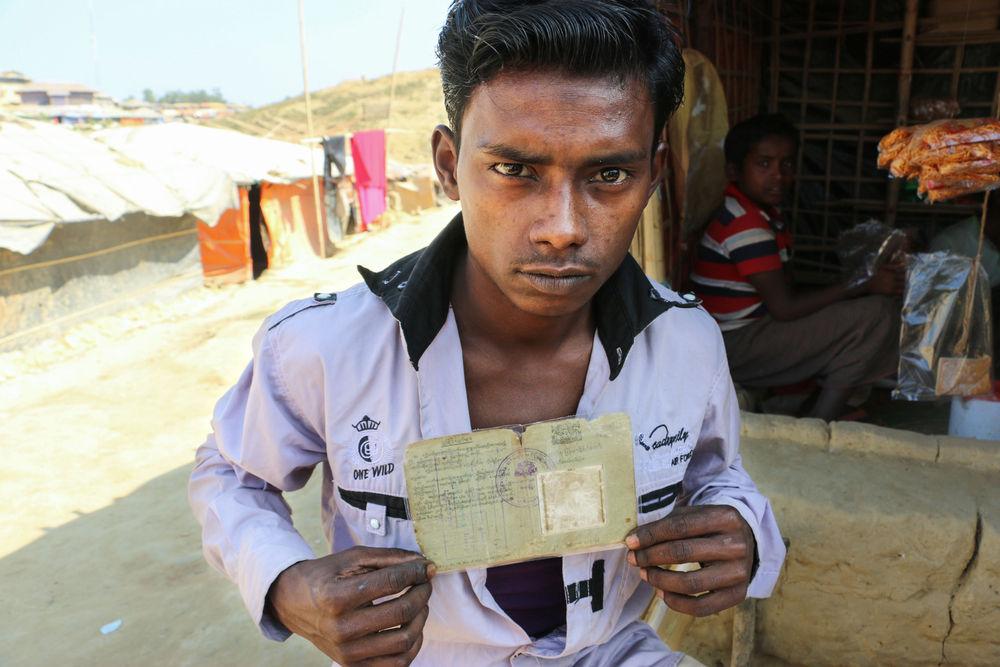 Nurul Hoque sealed his family's ID cards and old photos in plastic after arriving in Bangladesh. He keeps them under his pillow when he sleeps.