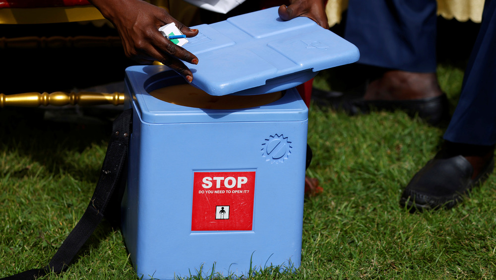 The image shows a blue ice box and mans hand taking the lid off the top.