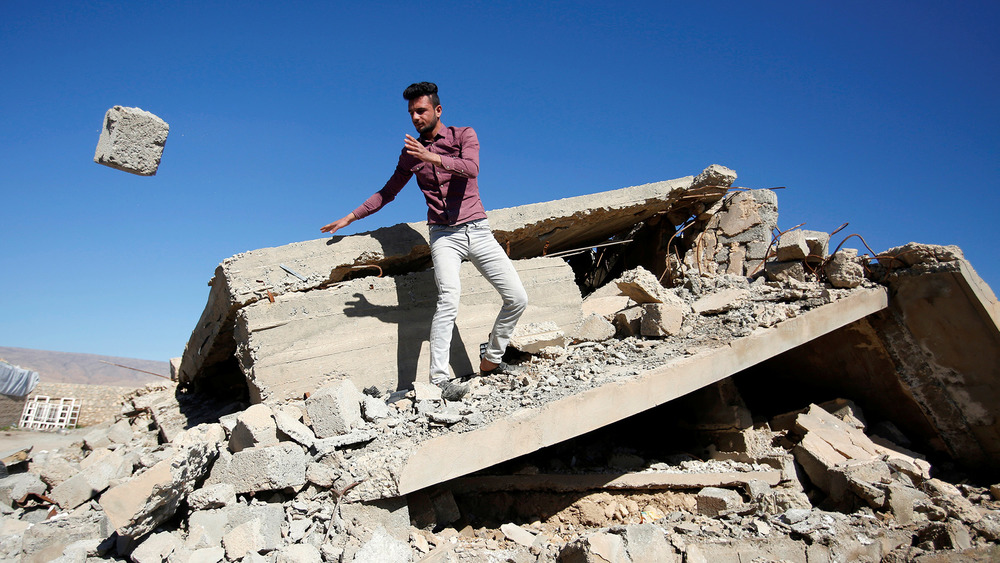 A man stands on a pile of rubble, a large stone he has thrown is in mid-air