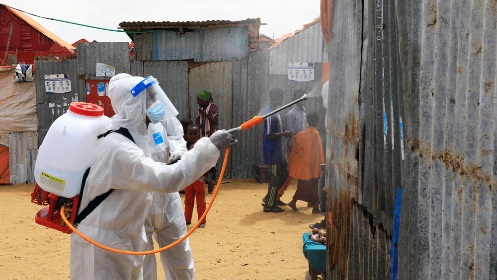 A man in a white suit holds a disinfectant spray nozzle and points it at the side of a temporary shelter.