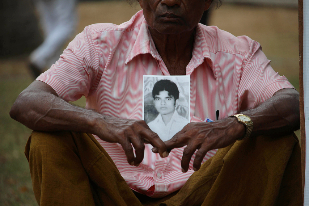 Families hold photographs of missing loved ones during a protest in Sri Lanka
