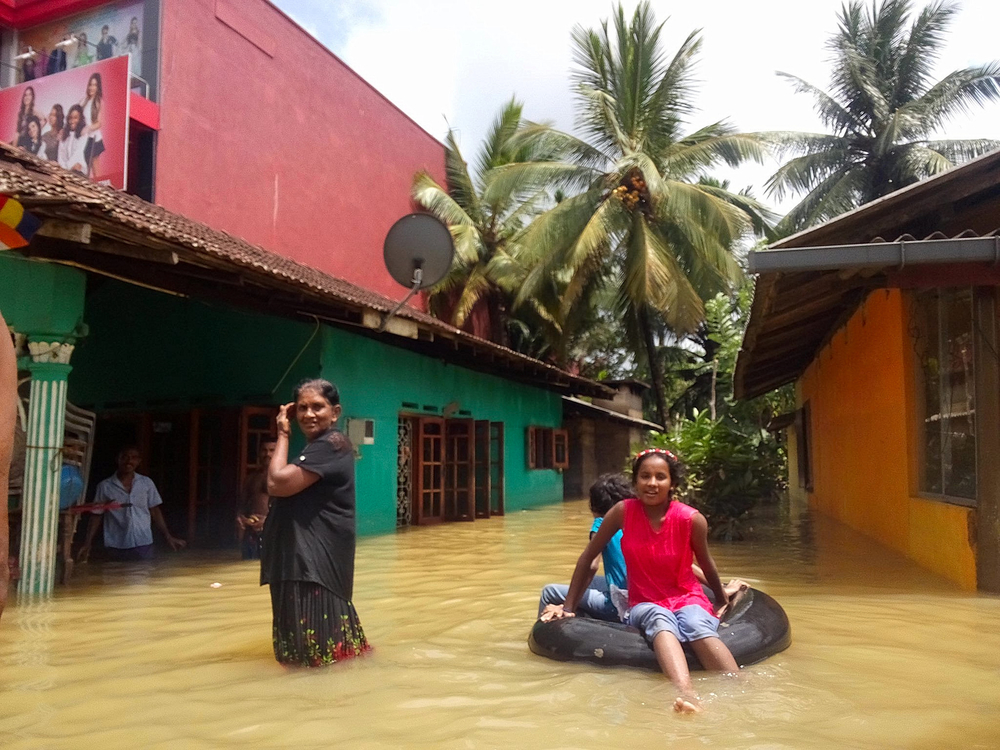 Residents of Udugama wade through flood waters on 27 May 2017, a day after 550mm of rain forced a nearby river to burst its banks