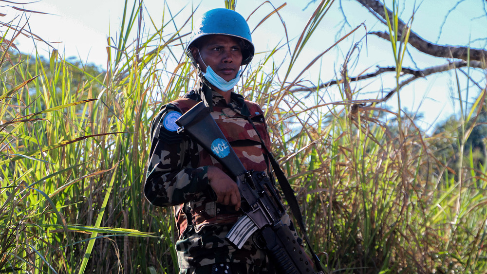 A woman in a blue UN helmet holds a rifle in front of a green field.