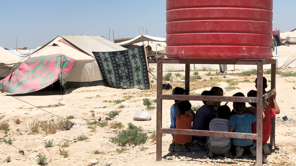 Children shelter from the sun at northeastern Syria's al-Hol camp in May. The camp is now home to nearly 69,000 people.