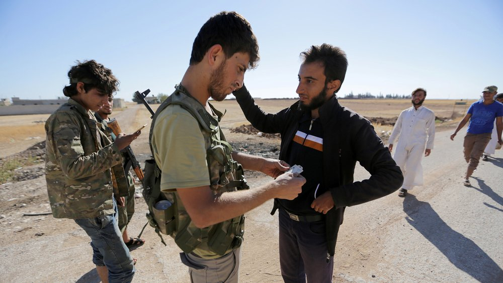 Rebel fighters inspect the identification papers of men in northern Syria