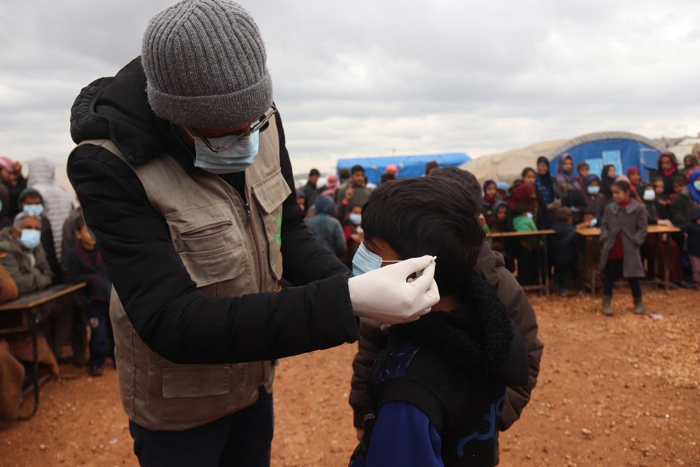 An aid worker shows a child how to put on a protective mask