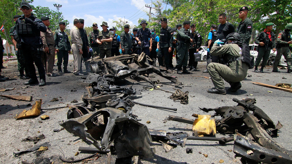 Security personnel inspect the site of a car bomb in Yala, Thailand