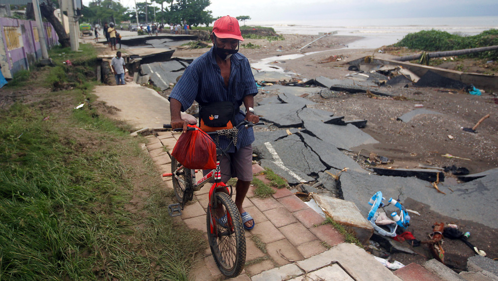 A man walks his bike along a road that has been damaged by flooding and heavy rains.