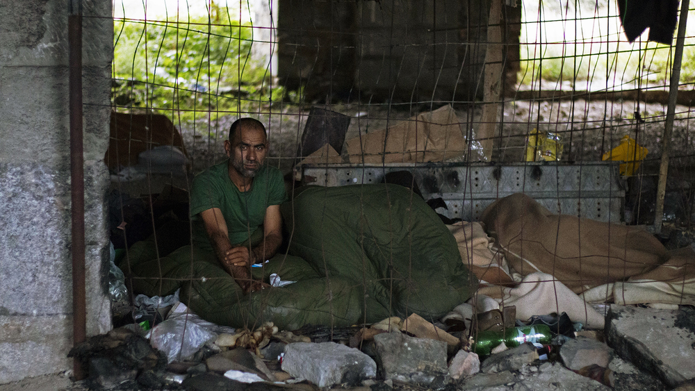 An asylum seeker from Pakistan sits in the abandoned building near the Trieste railway station that has become a makeshift shelter