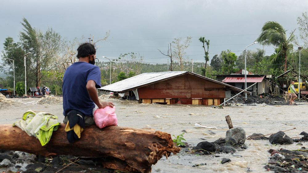 A man looks at his house buried under the pile of rubble and sand following flash floods brought by Typhoon Goni in Barangay Busay, Daraga town, Albay province, Philippines on 1 November, 2020.
